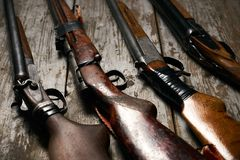 Ollection of hunting rifles. Rifles, shotguns on wooden table background, Hunting guns close-up Stock Photo