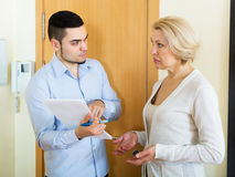Сollector to get the arrears. Сollector is trying to get the arrears from women at home door Royalty Free Stock Image