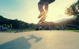 Ollie för Skateboarderbenövning på skateparkrampen Arkivbilder