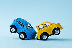 Сollision of two toy cars on a blue background Stock Photos