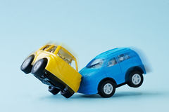 Сollision of two toy cars on a blue background Royalty Free Stock Photo