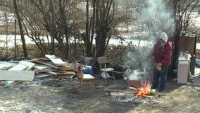 OLOMOUC,捷克, 2018年1月29日:无家可归的恶劣的灼烧的木委员会和创造火温暖自己在 股票录像