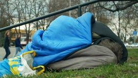 OLOMOUC, CZECH REPUBLIC, JANUARY 2, 2019: Homeless asleep and sleep in sleeping bag on street near department store royalty free stock images