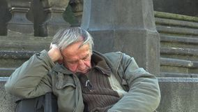 OLOMOUC, CZECH REPUBLIC, JULY 3, 2015: Authentic emotion homeless man senior asleep and awakening. Authentic emotion homeless man senior asleep and awakening at stock video footage