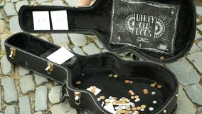 Olomouc, Czech Republic, May 29, 2019: City begging money coins into case, authentic plays music the guitar square