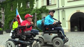OLOMOUC, CZECH REPUBLIC, MAY 9, 2018: Two invalid men on an electric modern wheelchair, the authentic situation of the. Two invalid men on an electric modern stock footage