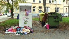 OLOMOUC, CZECH REPUBLIC, OCTOBER 20, 2017: Authentic homeless poor woman looking eats food from trash bin and the. Authentic homeless poor woman looking eats stock video footage