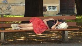 Olomouc, República Checa 1º de agosto de 2016: menina autêntica da emoção adormecida em um banco no parque filme