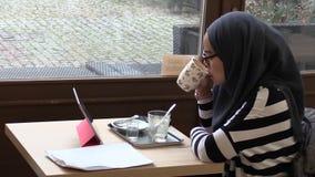 OLOMOUC, REPÚBLICA CHECA, EL 17 DE DICIEMBRE DE 2017: Una mujer que estudia al estudiante que estudia el texto del ipad y que beb almacen de video