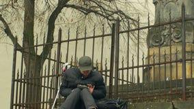 OLOMOUC, REPÚBLICA CHECA, EL 2 DE ENERO DE 2018: Auténtico pobre del hombre sin hogar con el ipad que juega, estatua histórica de almacen de metraje de vídeo