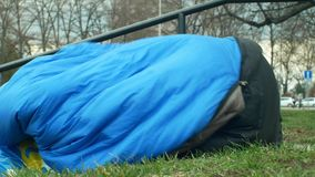 OLOMOUC, REPÚBLICA CHECA, EL 2 DE ENERO DE 2019: Dormido sin hogar y despierta de sueño en saco de dormir en la calle auténtica metrajes