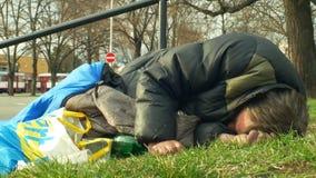 Olomouc, República Checa, el 2 de enero de 2019: Dormido sin hogar y despierta de sueño despierta en saco de dormir en la calle almacen de metraje de vídeo