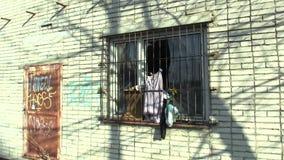 OLOMOUC, REPÚBLICA CHECA, EL 18 DE ENERO DE 2018: La ventana sin hogar del ghetto con la pintada de las rejillas, morando en mili metrajes