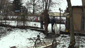 Olomouc, República Checa, el 30 de enero de 2018: Los más viejos hombres sin hogar toman a carro los tableros de madera y las pue almacen de metraje de vídeo