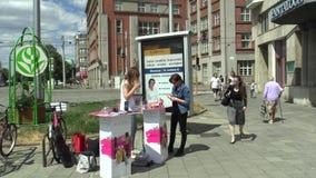 OLOMOUC, REPÚBLICA CHECA, EL 5 DE JULIO DE 2018: Oferta de mujeres jovenes para los cosméticos del perfume de la venta en la call metrajes
