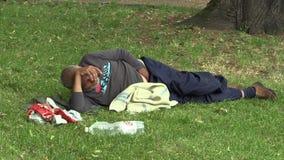 Olomouc, República Checa, o 5 de maio de 2018: As mentiras desabrigadas do homem da cara autêntica da emoção relaxam no parque na filme