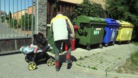 OLOMOUC, REPÚBLICA CHECA, O 5 DE MAIO DE 2018: Os pobres desabrigados escolhem um lixo do escaninho do recipiente de papel do cai video estoque