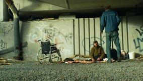 Olomouc, República Checa, o 24 de outubro de 2018: Grupo da emoção dos sem-abrigo autêntico e de uma cadeira de rodas inválidos s video estoque