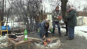 OLOMOUC, REPUBBLICA CECA, IL 29 GENNAIO 2018: Bordo di legno bruciante difficile degli uomini senza tetto e fuoco creare per risc stock footage