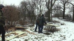 Olomouc, repubblica Ceca, il 30 gennaio 2018: Gli uomini più anziani senza tetto prendono a trasporto i bordi di legno e le porte stock footage