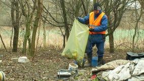 OLOMOUC, REPUBBLICA CECA, IL 2 GENNAIO 2019: L'uomo raccoglie i rifiuti dell'immondizia riunisce la borsa, paesaggio della forest archivi video