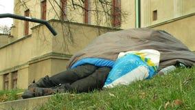 OLOMOUC, REPUBBLICA CECA, IL 2 GENNAIO 2019: Risveglio del senzatetto che si trova sulla terra nel parco da un altro senzatetto stock footage