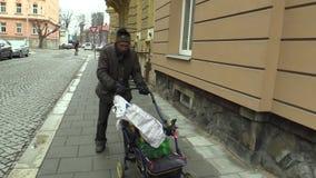 Olomouc, repubblica Ceca, il 5 marzo 2018: Un uomo senza tetto povero autentico cammina giù la via con un trasporto del carretto  archivi video