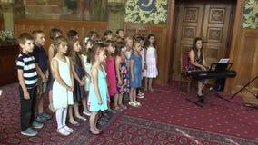 OLOMOUC, TSJECHISCHE REPUBLIEK, 15 APRIL, 2018: De kinderen van het koorrefrein het zingen van zingt Tsjechisch oud volkslied Oko stock video