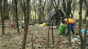 OLOMOUC, TSJECHISCHE REPUBLIEK, 2 JANUARI, 2019: De mens verzamelt huisvuilnad vuilnis verzamelt zak, boslandschap in bedreigd stock videobeelden