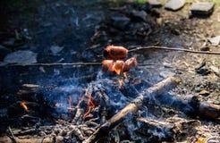 Olor ahumado de la comida asada Cómo asar las salchichas Salchichas en el palillo con la hoguera y humo en fondo Roasty imágenes de archivo libres de regalías