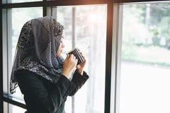 Olor musulmán asiático de la mujer de negocios y café de consumición fotos de archivo libres de regalías