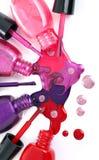 Сolored nail polish splash, spilling from bottles Stock Photos