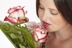 Olores morenos atractivos jovenes de la mujer en las rosas foto de archivo libre de regalías