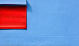 Сolorful blue wall. Closed red window on colorful blue wall Royalty Free Stock Photos