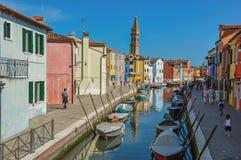 Olorful byggnader, torn, folk och fartyg framme av en kanal på Burano Fotografering för Bildbyråer