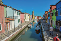 Olorful byggnader, torn, folk och fartyg framme av en kanal på Burano Arkivfoto