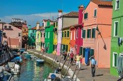 Olorful byggnader, torn, folk och fartyg framme av en kanal på Burano Royaltyfria Foton