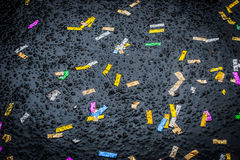 Сolorful confetti on the wet asphalt background Royalty Free Stock Photo