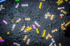 Сolorful confetti on the wet asphalt Stock Photography