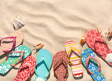 Сolorful flip flops on the sandy beach. Holydays background. Copy space for your text. Top view Royalty Free Stock Photography