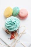Olorful macaroons Ð ¡ με το cupcake και το παρόν στο υπόβαθρο Στοκ Εικόνες