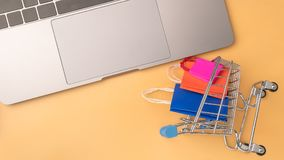 Olorful paper shopping bag and trolley go down from floating royalty free stock photo