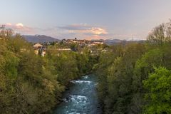 Oloron river and Oloron-Sainte-Marie city in sunset light. Mountains of French Atlantic Pyrenees are at background royalty free stock image