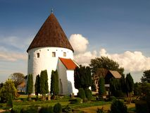 Ols kirke. The third church-rotunda built around the year 1250 of the Danish island of Bornholm. Near the temple is visible withered with age tree-freak Royalty Free Stock Photo