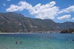 Oludeniz, die Türkei - 10. Juli 2012: Leute, die das Schwimmen im wunderbaren reinen Ägäischen Meer auf türkischer Küstenlinie ge Stockfotos