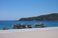 Oludeniz, die Türkei - 10. Juli 2012: touristische Boote auf dem Ufer auf wunderbarem Strand auf türkischem Küstenlinie oludeniz Lizenzfreies Stockbild