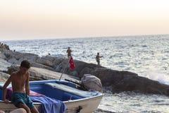 OLUDENIZ - FETHIYE, TURKIJE - 24 AUGUSTUS 2018 De schone spruit van een jongen zit op het zeil in de zonsondergangtijd royalty-vrije stock fotografie