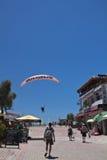 Oludeniz, Turkey - July 10, 2012: tourists walking in town, man landing in parachute on oludeniz beach in summertime Stock Photography