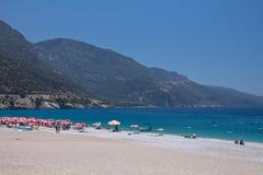 Oludeniz Turkiet - Juli 10, 2012: turister som spenderar deras sommarferier som tycker om att simma och att solbada på den underb Arkivbild