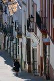 Olvera, Cadiz provincie, Andalusia, Spanje - Maart 25, 2008: vrouw met het winkelen in Calle Maestro Amado stock foto's